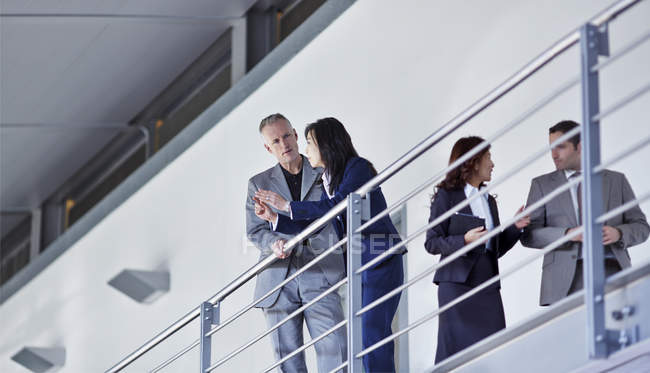 Business people talking at railing n office — Stock Photo