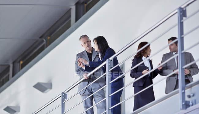 Les gens d'affaires parlent au bureau de garde-corps n — Photo de stock