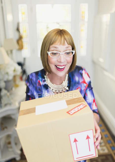 Surprised mature woman receiving package — Stockfoto