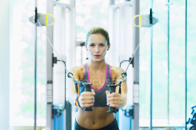 Focused woman using cable exercise equipment at gym — Stock Photo