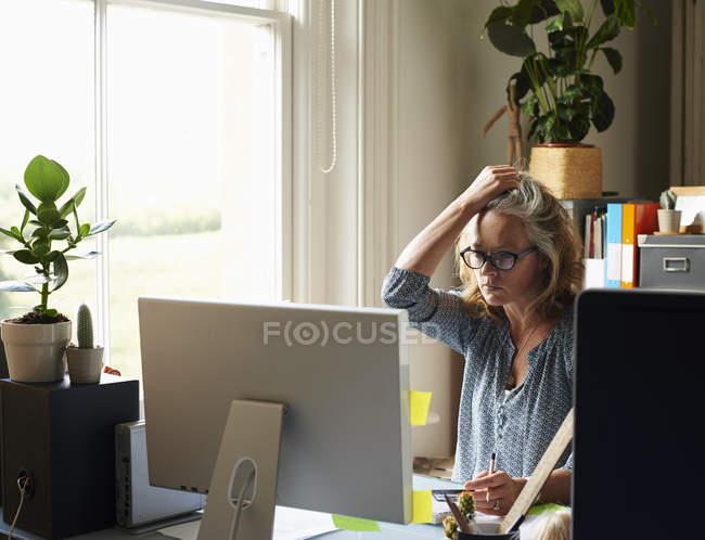 Підкреслив жінка з руки в волосся, тримаючи кредитної картки на комп'ютері в домашній офіс — стокове фото