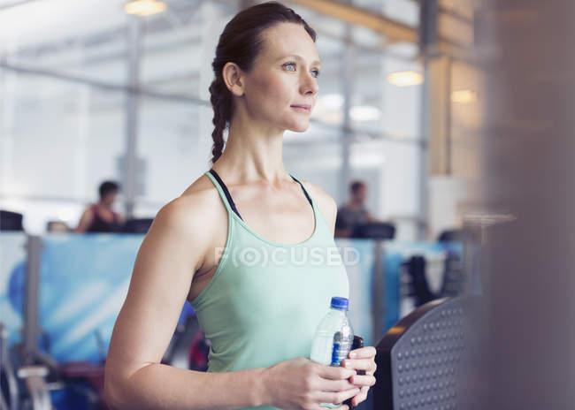 Nachdenkliche Frau Trinkwasser in Turnhalle — Stockfoto