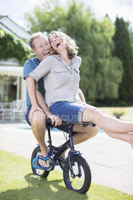 Coppia equitazione piccola bicicletta in erba — Foto stock
