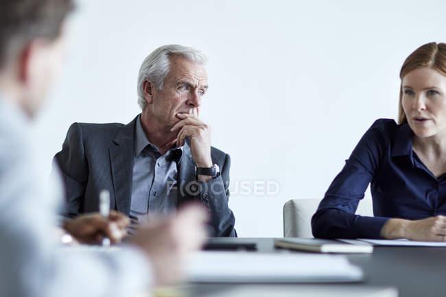 Attentif homme d'affaires senior, écouter de la femme d'affaires en réunion — Photo de stock
