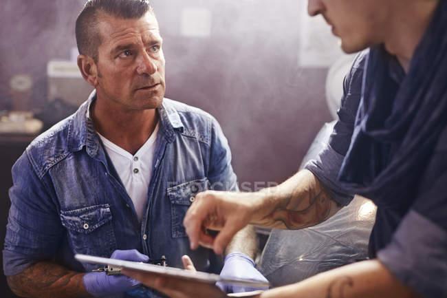 Mann mit digital-Tablette im Gespräch mit Tätowierer im studio — Stockfoto