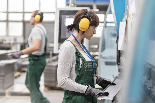 Female worker with ear protectors holding metal part in factory — Stock Photo