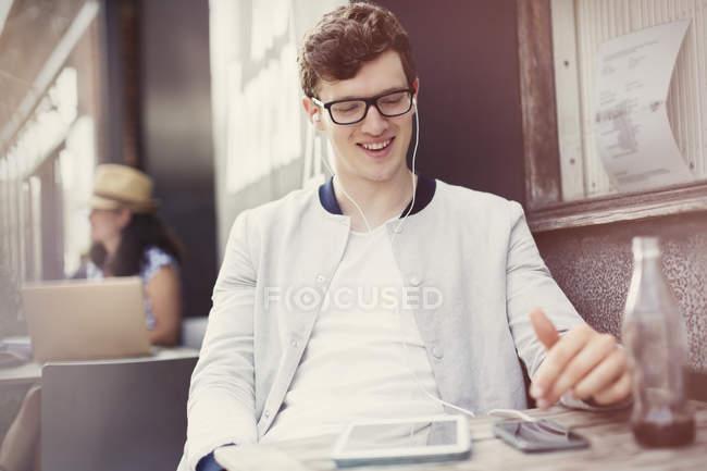 Jeune homme souriant écoutant de la musique avec écouteurs et lecteur mp3 au café trottoir — Photo de stock