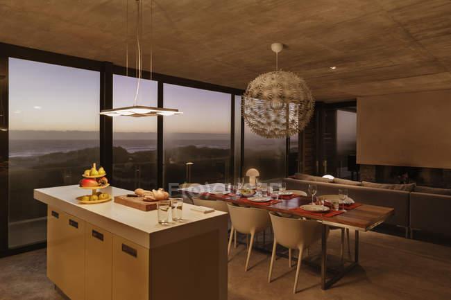 Сніданок бар і обідній стіл сучасної кухні з видом на океан в сутінках — стокове фото