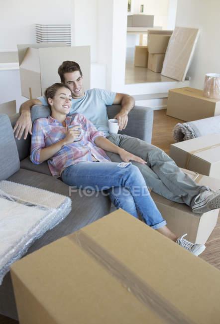 Couple de détente avec café sur le canapé dans Maison Neuve — Photo de stock