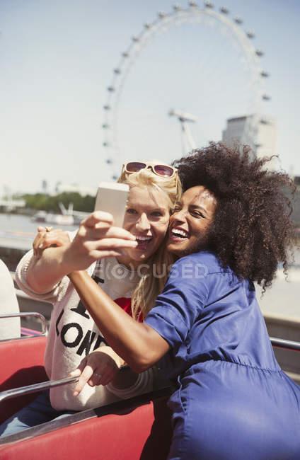 Amis enthousiastes prenant selfie en bus à deux étages avec London Eye en arrière-plan — Photo de stock