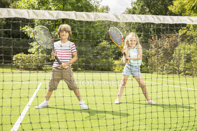 Children playing tennis on grass court — Stock Photo