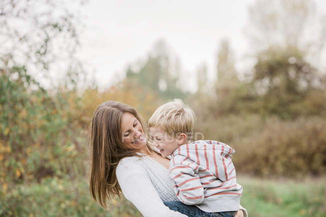 Mother and toddler son laughing in autumn park — Stock Photo
