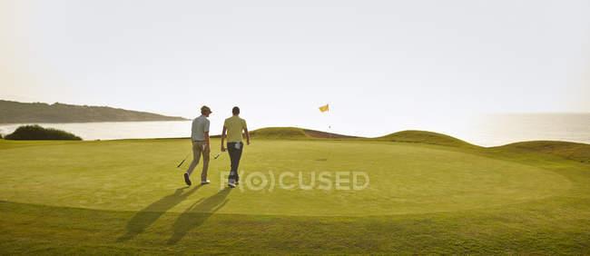 Homens caucasianos caminhando no campo de golfe — Fotografia de Stock