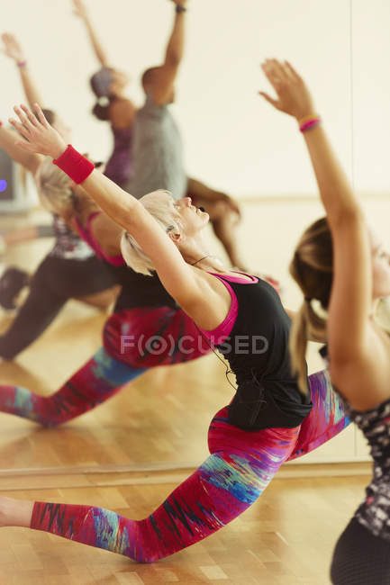 Fitness instructor leading class in low lunge — Stock Photo