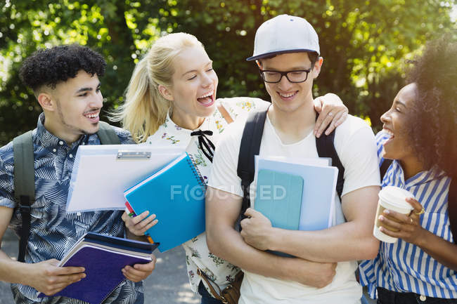 Enthusiastic college students joking friend outside — Stock Photo