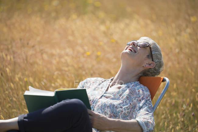 Donna anziana che legge libro e ride con la testa indietro nel campo soleggiato — Foto stock