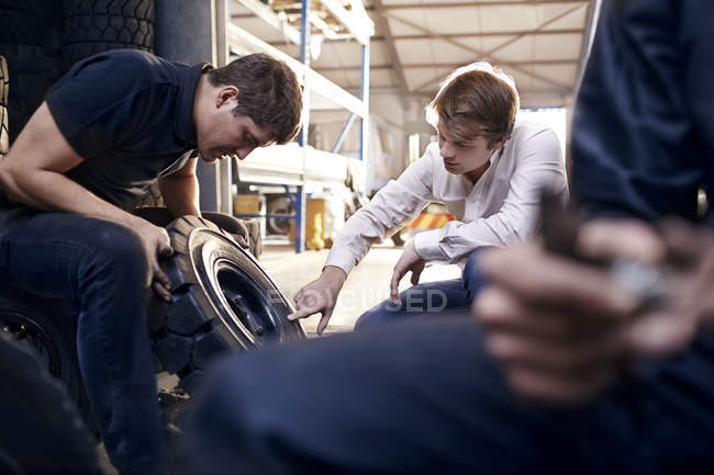 Mechanic and customer examining tire in auto repair shop — Stock Photo