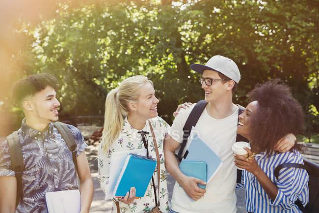 Étudiants avec livres et café marche dans le parc — Photo de stock