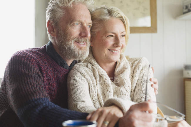 Smiling senior couple hugging and looking away — Stock Photo