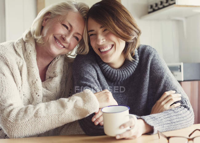 Laughing mother and daughter in sweaters hugging and drinking coffee — Stock Photo