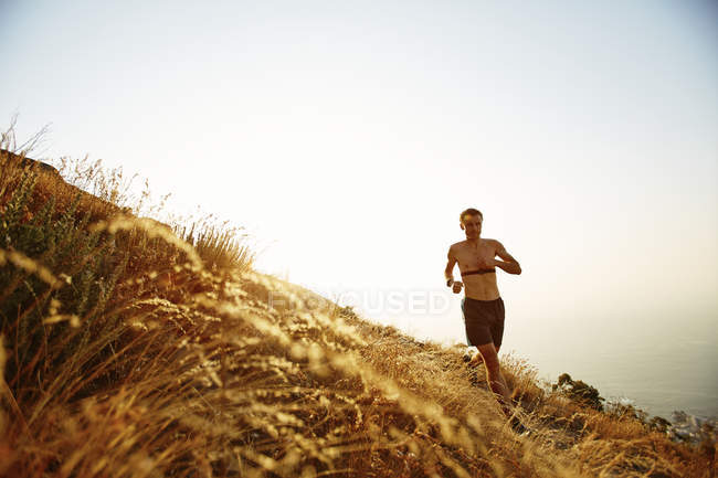Bare chested man running on sunny hillside — Stockfoto