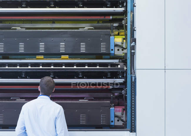 Engenheiro olhando para máquinas de prensa na planta de impressão — Fotografia de Stock