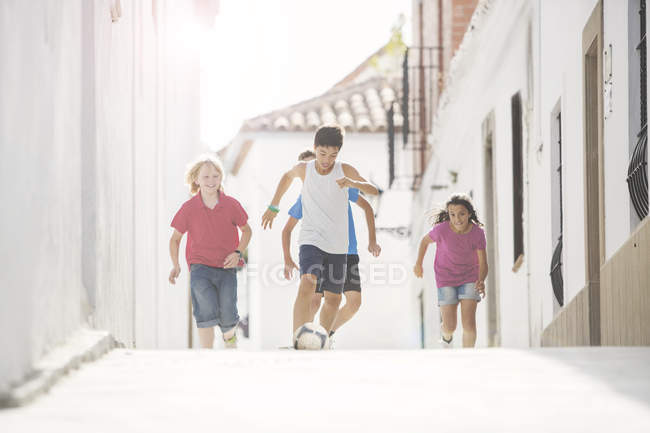 Children playing soccer in alley — Stock Photo