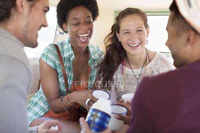 Friends drinking tea in van — Stock Photo