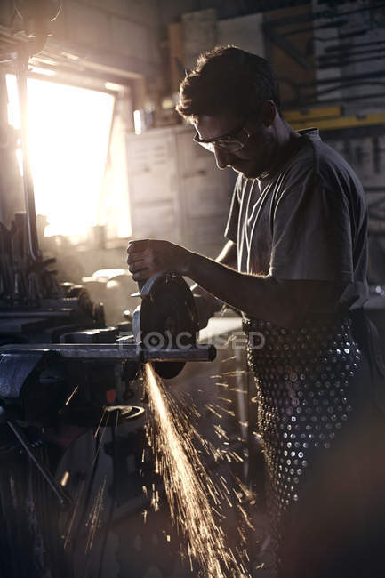 Blacksmith using saw in forge — Stock Photo