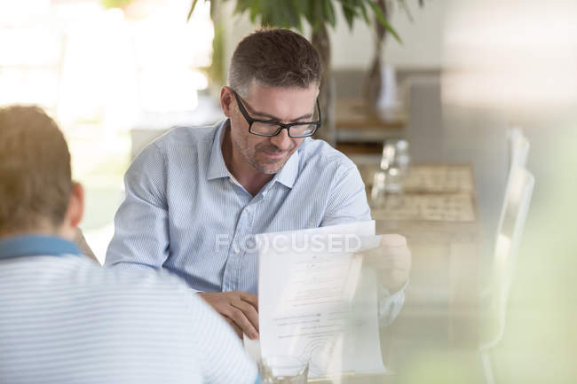 Businessman reviewing notes in cafe — Stockfoto