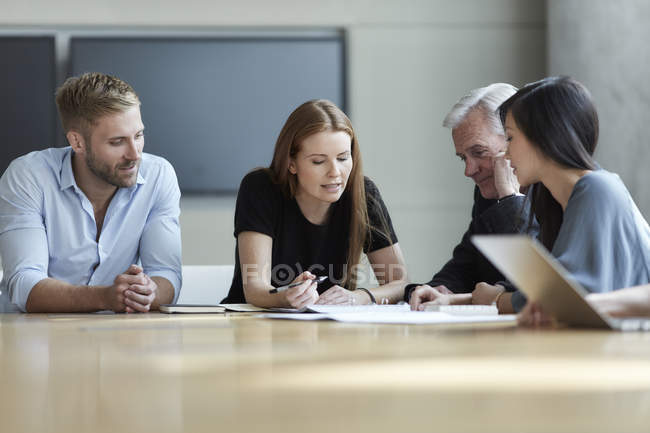 Business people reviewing paperwork in meeting — Stock Photo