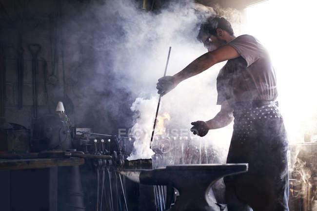 Blacksmith heating iron tool in forge — Stock Photo
