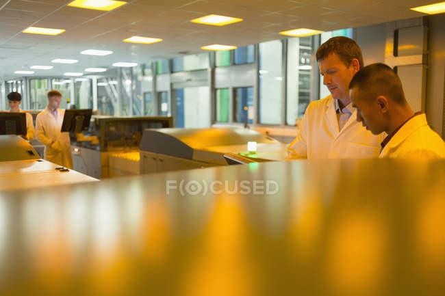 Engineer among printers in printing plant — Stock Photo