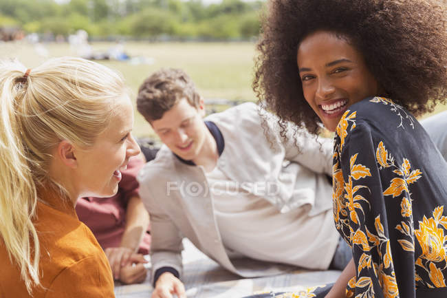 Portrait smiling woman hanging out with friends in sunny park — Stock Photo