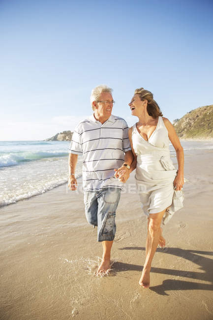 Senior couple walking in surf on beach — Stock Photo