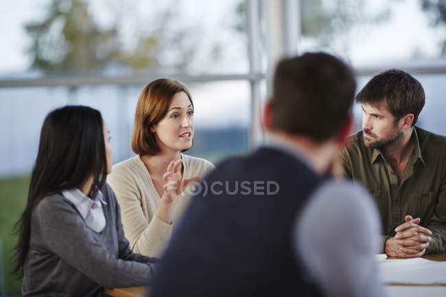 Gente de negocios adultos de éxito hablando en reunión - foto de stock