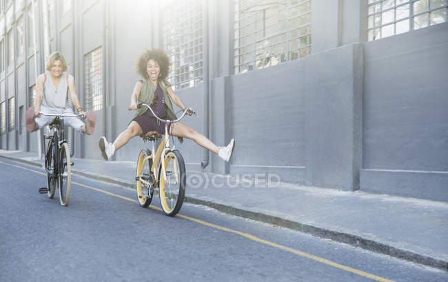 Playful women coasting on bicycles down urban street — Stock Photo