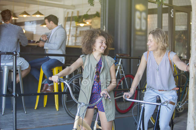 Smiling women on bicycles outside cafe patio — Stock Photo