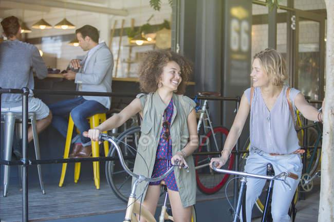 Lächelnde Frauen auf Fahrrädern Café Terrasse — Stockfoto