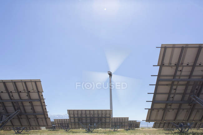 Wind turbine and solar panels in rural landscape — Stock Photo