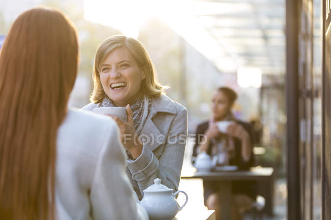 Women laughing and drinking tea at sidewalk cafe — Stock Photo
