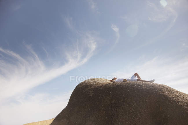 Uomo rilassante sulla formazione rocciosa — Foto stock