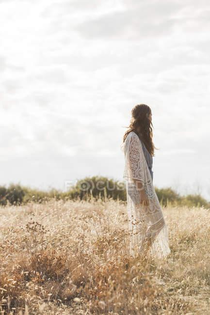 Serene boho femme debout dans le domaine rural — Photo de stock
