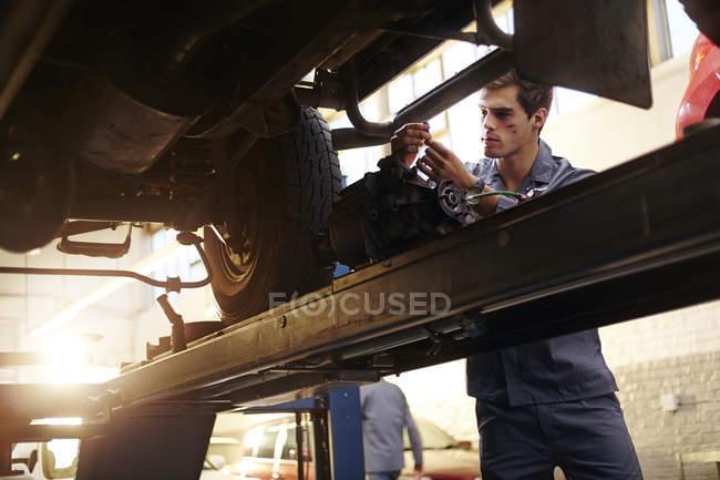 Механик, работающий под автомобилем в автомастерской — стоковое фото