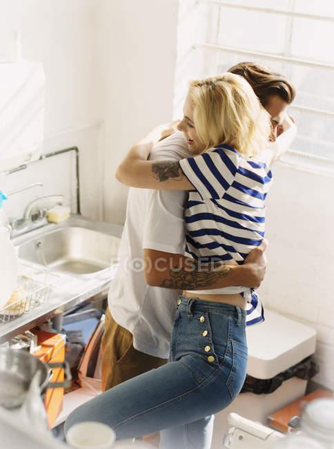 Junges Paar umarmt In Küche — Stockfoto