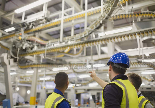 Workers discussing winding printing press conveyor belts overhead — Stock Photo