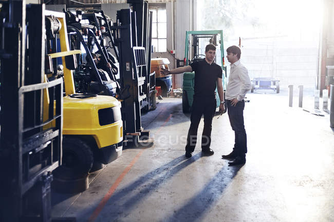 Mechanic and customer talking in auto repair shop — Stock Photo