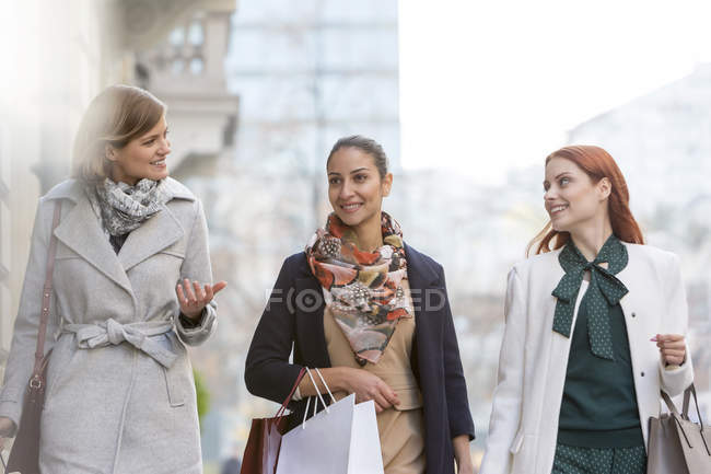 Mulheres com sacos de compras conversando e andando na cidade — Fotografia de Stock