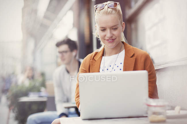 Donna che utilizza il computer portatile al caffè marciapiede — Foto stock