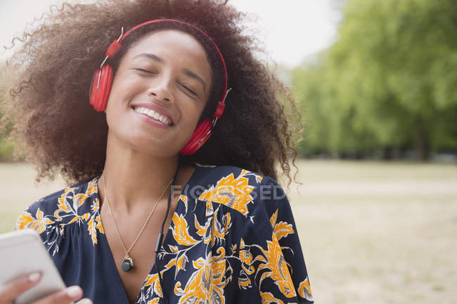 Enthusiastic woman listening to music with headphones and mp3 player in park — Stock Photo